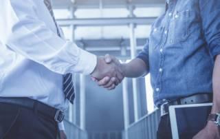 Business audit in server room. Business associates handshake.
