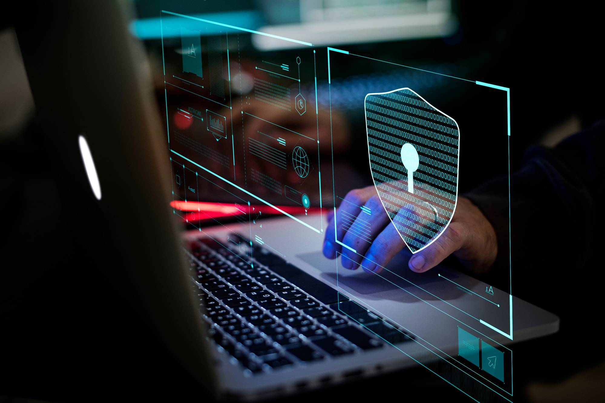 Hands typing on laptop with cyber security floating graphics.
